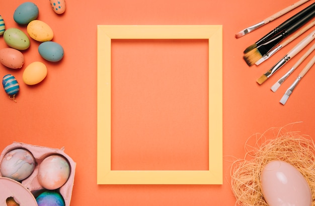 Yellow border frame surrounded with easter eggs; nest and paint brushes on an orange background Free Photo