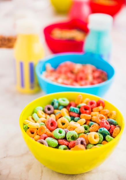 Yellow bowl of cereal with milk bottles Free Photo