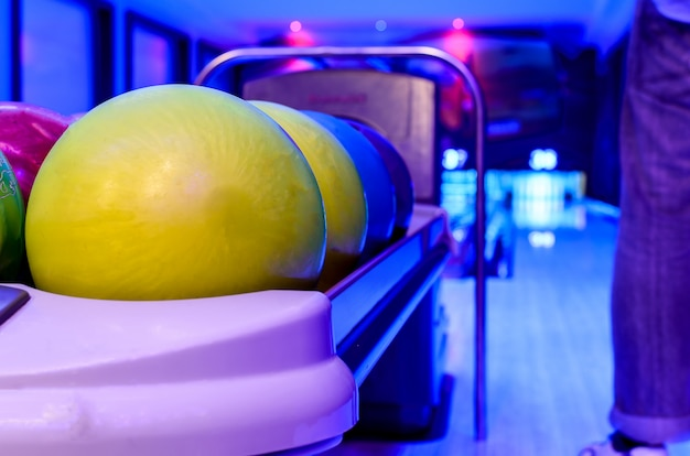 A yellow bowling balls has ready for player to throwing ball on the wooden lane Premium Photo