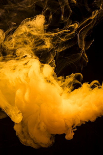 Yellow bright smoke clouds spread out wide against dark black background Free Photo