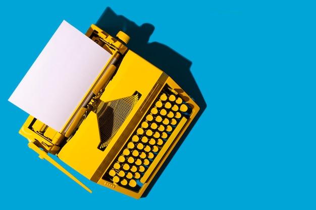 Желтая яркая пишущая машинка на синей поверхности Premium Фотографии
