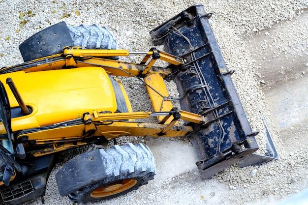 Yellow bulldozer, loading gravel for road construction Premium Photo