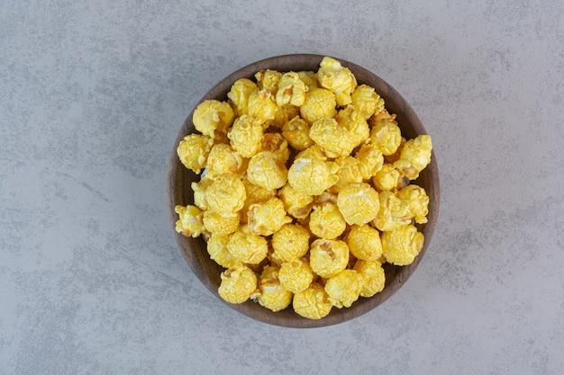 Mucchio ricoperto di caramelle gialle di popcorn su marmo. Foto Gratuite