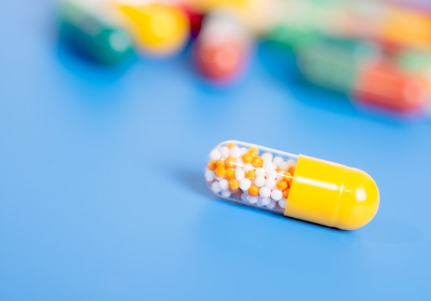Yellow capsule with medication on blue Premium Photo