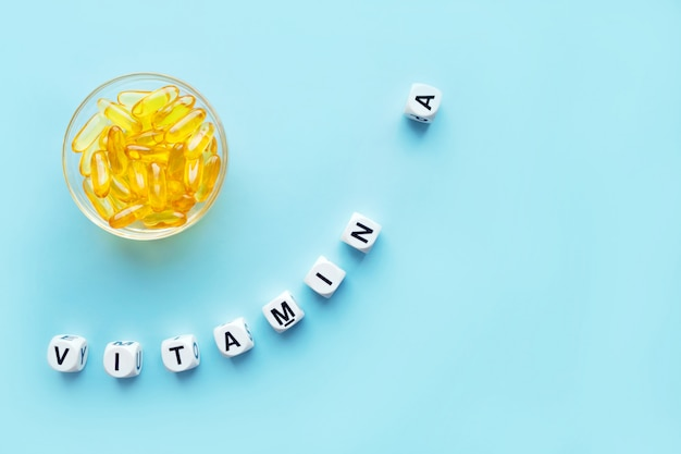 Yellow capsules in the round glass bowl and the word vitamin a Premium Photo