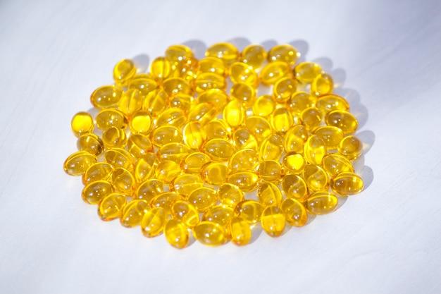 Желтые капсулы с витамином d, рыбий жир омега-3 с солнечным светом. здоровая и медицинская концепция. Premium Фотографии