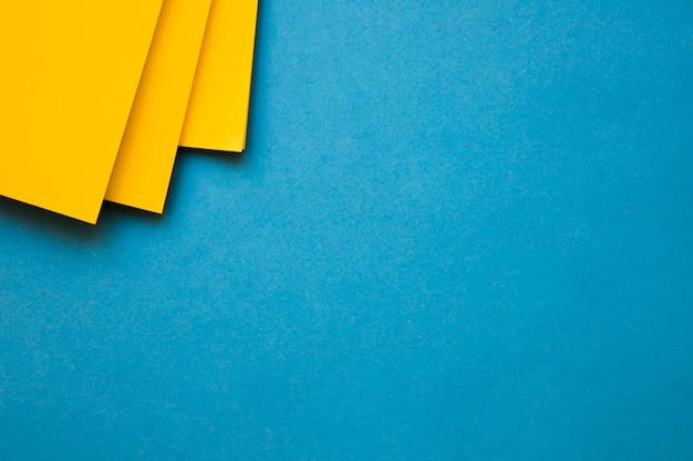 Carte di cartone giallo all'angolo del contesto blu Foto Gratuite