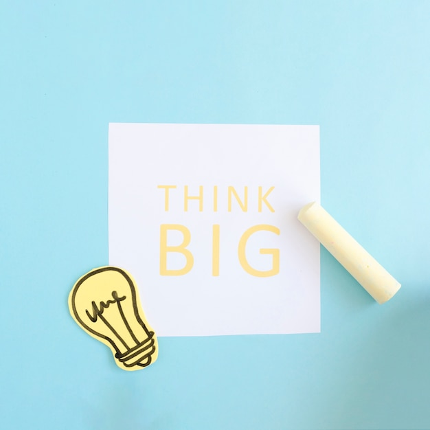 Yellow chalk and paper cutout light bulb on think big text over white paper on blue background Free Photo