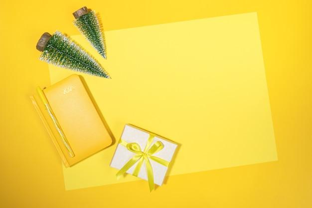 Желтый рождественский фон рабочего пространства. рамка желтого блокнота - органайзер на 2021 год, маленькие рождественские елки и подарочная коробка diy на желтом листе с местом для копирования. подведение итогов, планирование. вид сверху, плоская планировка. Premium Фотографии