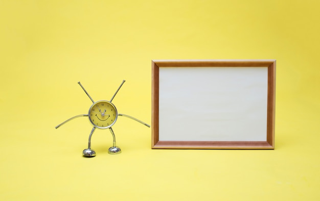 A yellow clock and a frame with an empty white sheet. clock and frame on a yellow space. yellow clock in the shape of a man. Premium Photo