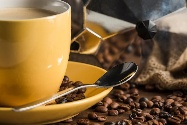 Yellow coffee set near beans and geyser coffee maker Free Photo