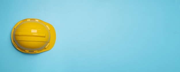 Yellow construction and protection helmet on blue wall Premium Photo