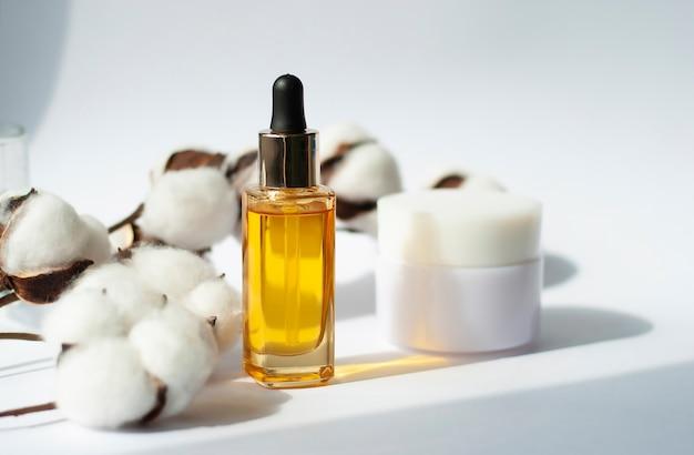 Желтая банка косметического масла и крема с хлопковой веткой Premium Фотографии