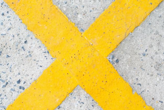 Yellow cross symbol on the road Premium Photo