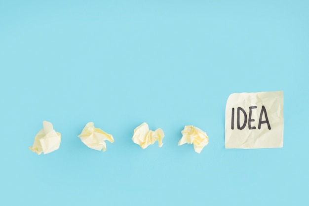 Yellow crumpled papers with idea text on the sticky note over the blue background Free Photo