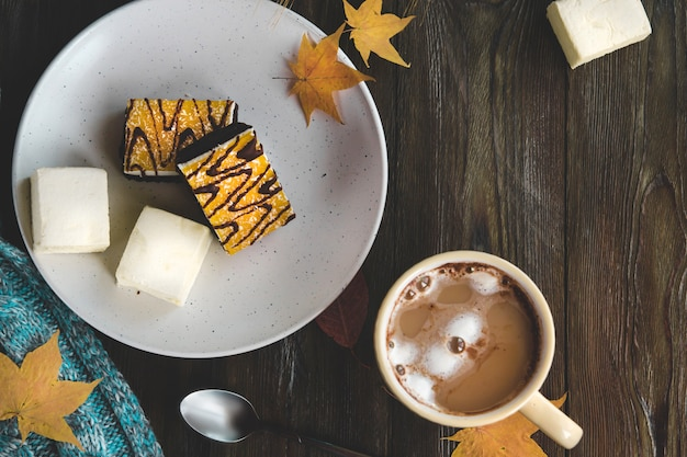Yellow cup of coffee with marshmallows and orange dessert on a white plate flat lay. Premium Photo
