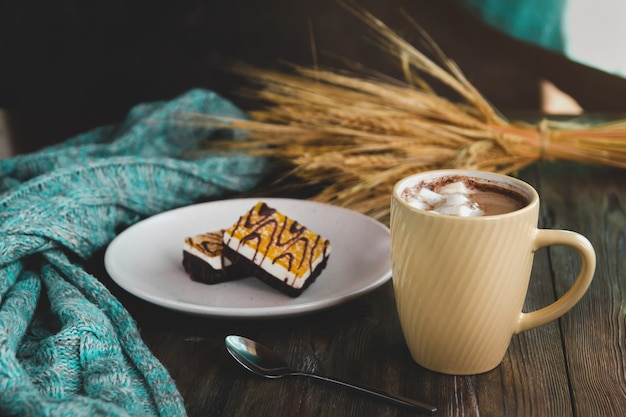 Yellow cup of coffee with marshmallows and orange dessert on a white plate. Premium Photo