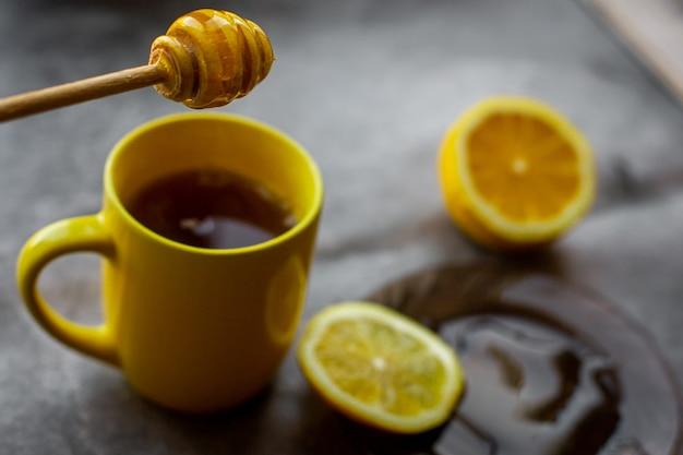 黄色いカップ、受け皿に蜂蜜を滴下、レモンと灰色の背景 Premium写真