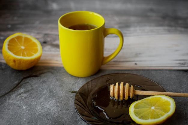 Желтая чашка, капающий мед на блюдце на сером Premium Фотографии