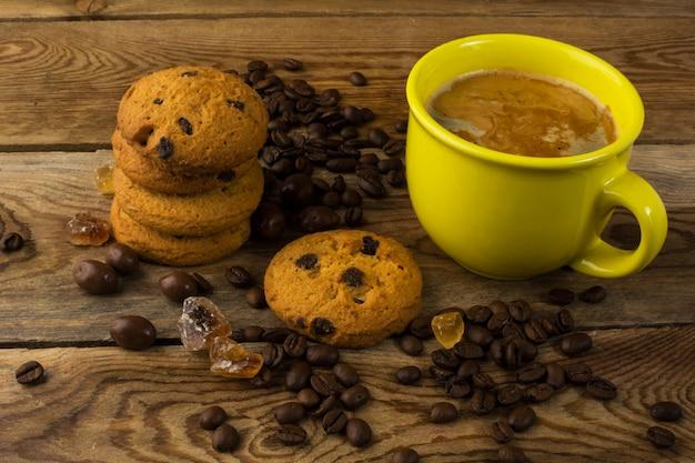濃いコーヒーとクッキーの黄色いカップ Premium写真