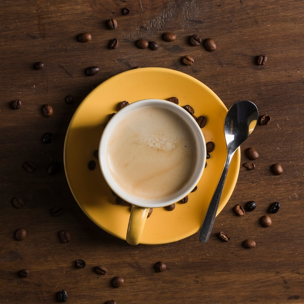 Yellow cup with beverage near coffee beans Free Photo