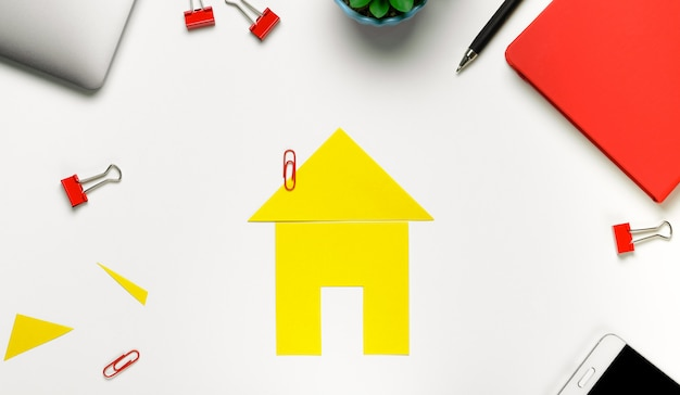 Yellow cut houset with office supplies Premium Photo