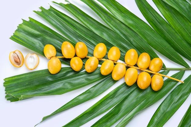 Желтые плоды финиковой пальмы, изолированные на белом фоне, куча свежих фруктов финиковой пальмы с фруктами финиковой пальмы на белом фоне Premium Фотографии