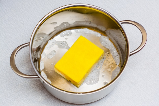 The yellow dishwashing sponge lies at the bottom of the soaped pan on the table. Premium Photo