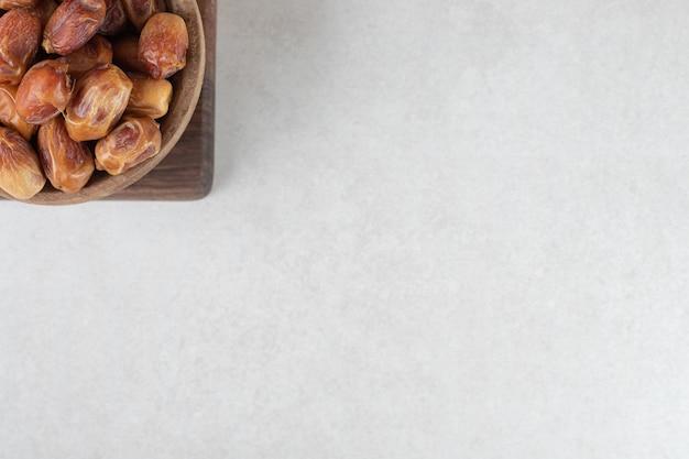 木製の大皿に黄色い乾燥ナツメヤシ。 無料写真