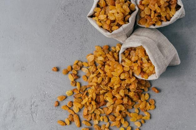 Yellow dry raisins spilled from textile sack Premium Photo