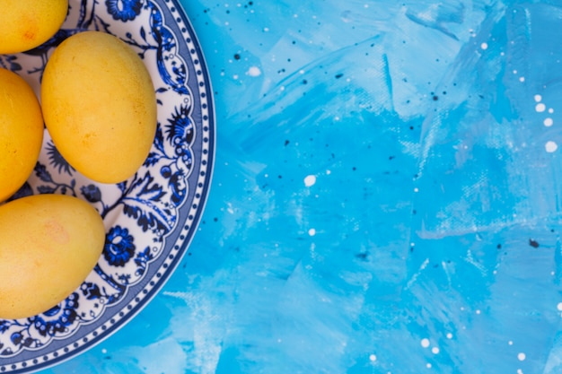 Yellow easter eggs on plate on table Free Photo