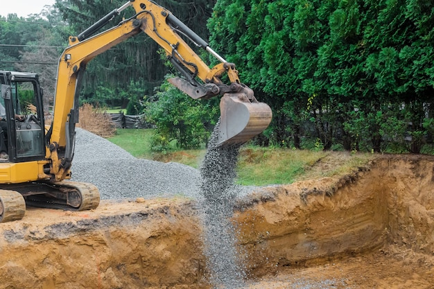 A yellow excavator bucket shovel moving stones gravel of foundation on a construction site Premium Photo