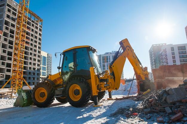 Желтый экскаватор зимой роет землю на стройке на фоне нового дома Premium Фотографии
