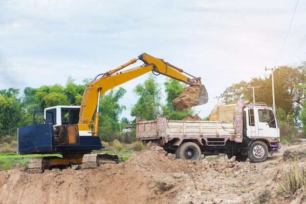 Yellow excavator machine loading soil into a dump truck at construction site Premium Photo
