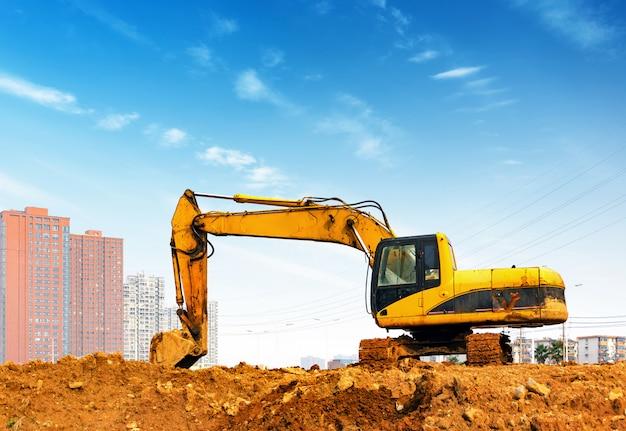 Yellow excavator on the site Premium Photo