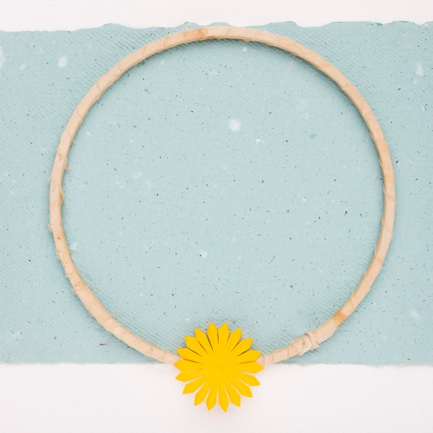 Yellow flower on the empty circular wooden frame over the paper Free Photo