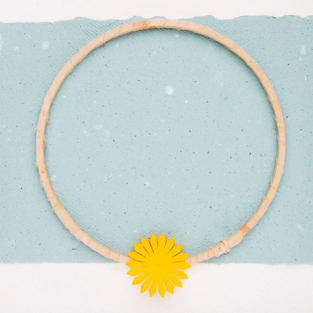 紙の上の空の円形木製フレームに黄色の花 無料写真