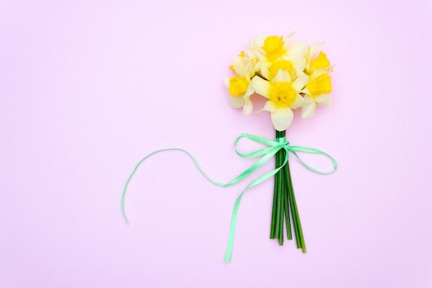 ピンクの背景に黄色い花。花束の水仙、春のギフトのコンセプト。 Premium写真