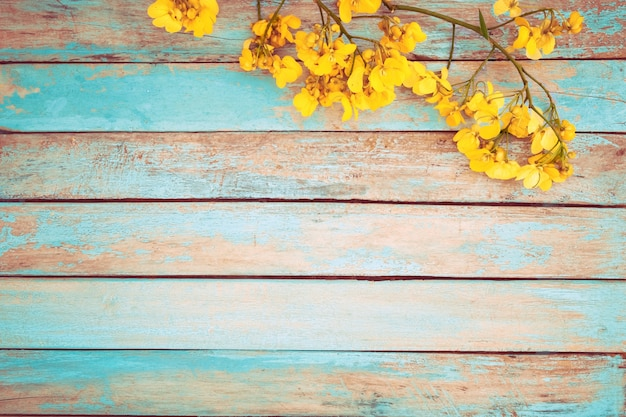 Yellow flowers wooden background, vintage color tone