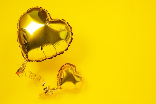 Yellow foil balloons in shape of heart on yellow Premium Photo