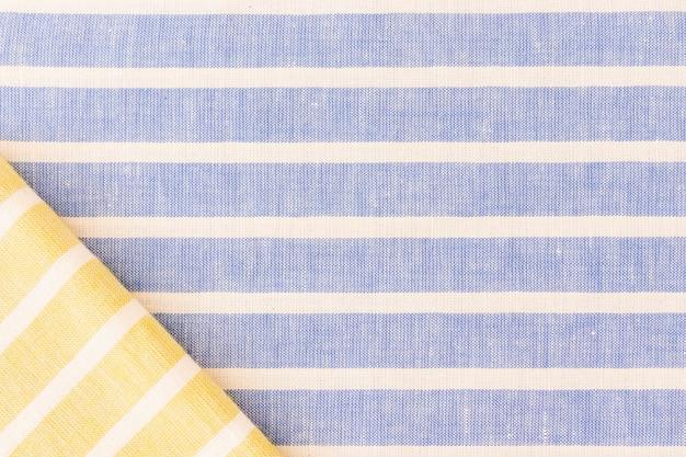 Yellow folded fabric on linen texture backdrop Free Photo