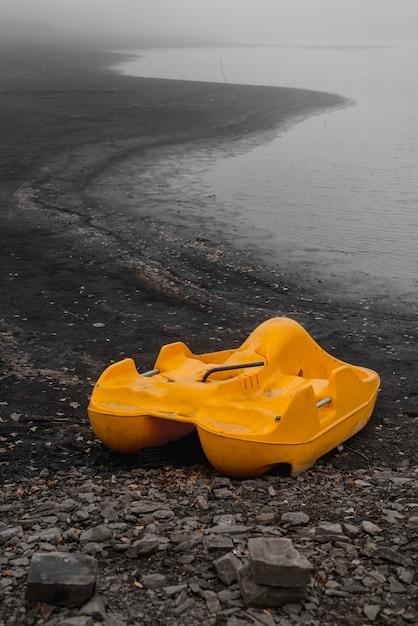 Желтый забытый катамаран одиноко стоит на берегу осенью Premium Фотографии