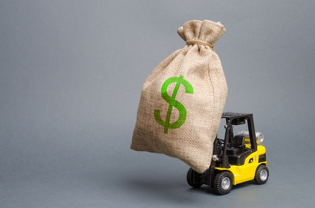 Yellow forklift truck carries a big bag of money. attracting investment in the development Premium Photo
