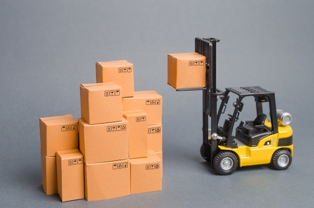 Yellow forklift truck raises a cardboard box to the top of a stack pile of boxes. warehouse, stock Premium Photo