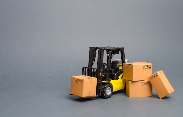 Yellow forklift truck with cardboard boxes. increase sales, production of goods. transportation Premium Photo