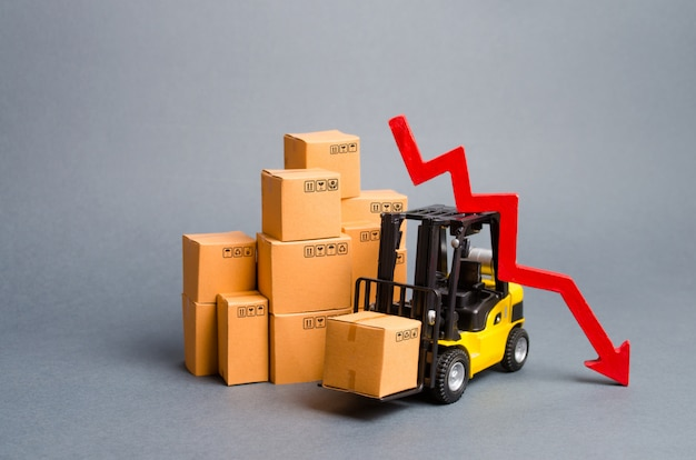 Yellow forklift truck with cardboard boxes and a red arrow down. drop in industrial production Premium Photo