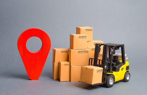 Yellow forklift truck with cardboard boxes and a red position pin. locating packages and goods Premium Photo