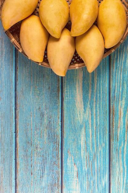 Yellow fresh mangos 0n blue wood table. mango tropical fruit. mangos. summer concept. Premium Photo