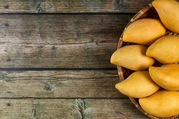 Yellow fresh mangos 0n wood table. mango tropical fruit. mangos. Premium Photo