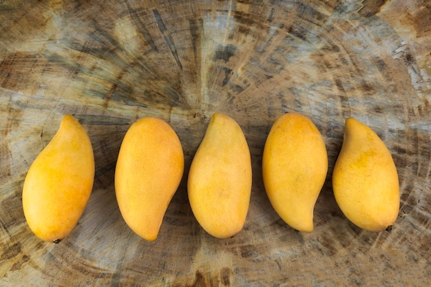 Yellow fresh mangos on real wood table. mango tropical fruit. Premium Photo